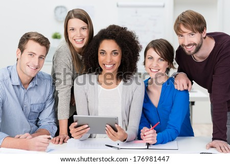 Successful motivated multiethnic business team posing grouped around an attractive African American woman looking at the camera with beaming friendly smiles - stock photo