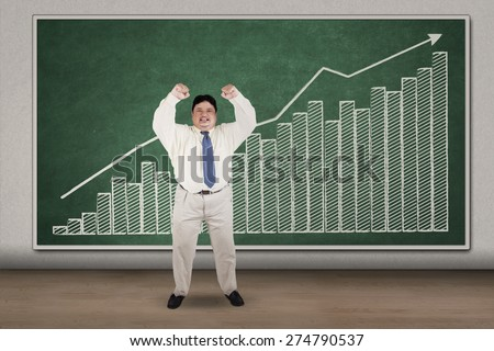 Successful overweight businessman, and financial graph on the blackboard - stock photo
