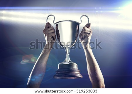Successful rugby player holding trophy against spotlights - stock photo