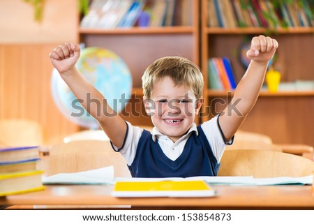 Successful schoolboy with hands up sitting at desk in classroom - stock photo