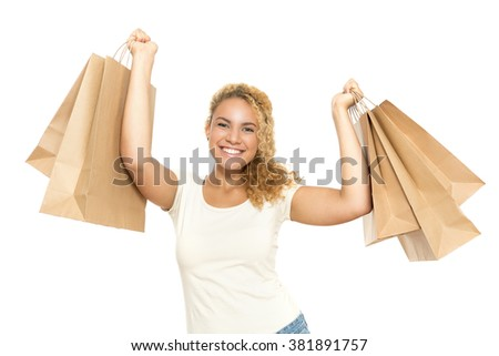 Successful shopping. Waist up portrait of a young tanned girl with curvy dyed hair standing smiling happily and holding many paper bags, isolated on white background - stock photo