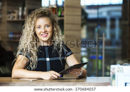 Successful small business owner standing at the bar and holding a tablet cancers - stock photo