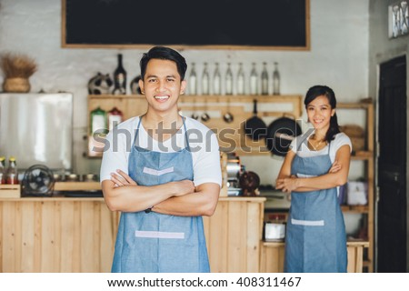 Successful small business owner standing with crossed arms with partner at the background - stock photo