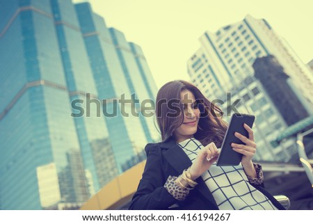 Successful smart business woman looking confident and smiling holding tablet computer - stock photo