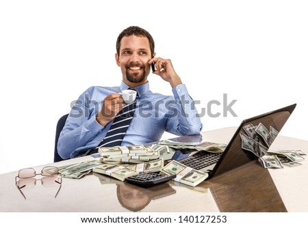 Successful smiling businessman relaxing and drinking coffee with a lot of dollar stacks at the desk isolated on white background - stock photo