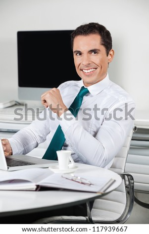 Successful smiling manager working with laptop in his office - stock photo