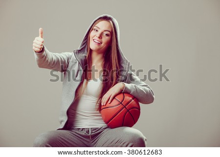 Successful sporty teenager girl wearing hooded sweatshirt holding basketball with thumb up gesture. Teen sport. - stock photo