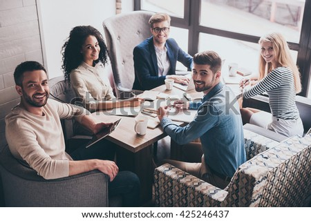 Successful team. Cheerful young people looking at camera with smile while sitting at the office table on business meeting - stock photo