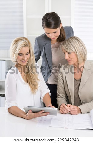 Successful team of female business people looking at tablet computer for a presentation. - stock photo
