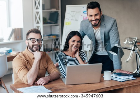 Successful team. Three confident business people in smart casual wear looking at camera and smiling while sitting at the desk in office  - stock photo