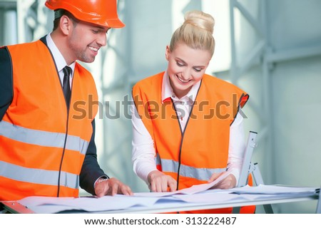 Successful two architects are discussing their project. They are standing near the table and looking at the blueprint with inspirations. The man and woman in workwear are smiling - stock photo