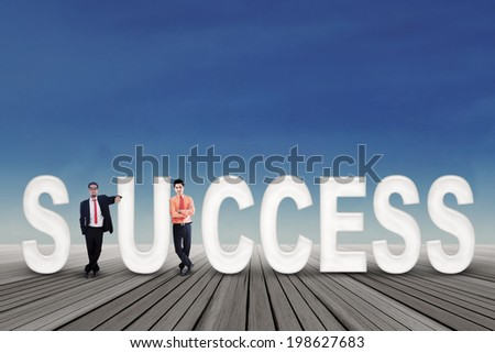 Successful two businessmen standing outdoors with a text of success - stock photo