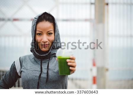 Successful urban sporty woman taking a rest for drinking nutritive detox smoothie. Fitness nutrition and healthy lifestyle concept. - stock photo