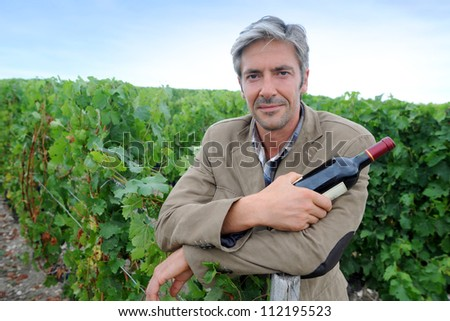 Successful winemaker in vineyard with bottle of red wine - stock photo