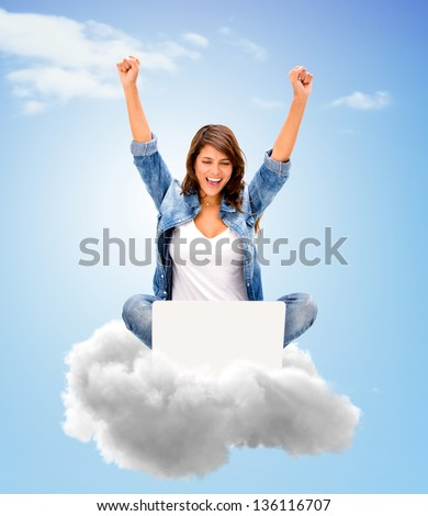 Successful woman using cloud computing with her laptop - stock photo