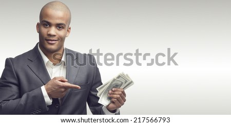 successful young african businessman standing over gray background - stock photo