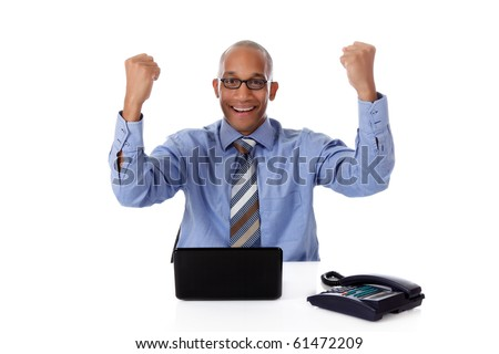 Successful young attractive African American businessman in office sitting against desk with a laptop and telephone. Happy clenching fists. Studio shot. White background. - stock photo