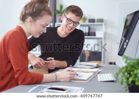 Successful young business partners working as a team sitting together at a desk checking paperwork and brainstorming - stock photo