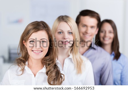 Successful young business team standing in an oblique row smiling at the camera with focus to a beautiful woman in the front with leadership qualities - stock photo