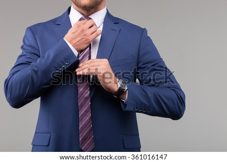 Successful young businessman is preparing for meeting. He is standing and adjusting his tie. Isolated on grey background - stock photo