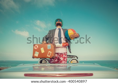 Successful young businessman on a beach. Man standing in the cabriolet classic car. Summer vacations and travel concept. Toned image - stock photo