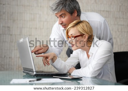 Successful young businesspeople with laptop in office - stock photo