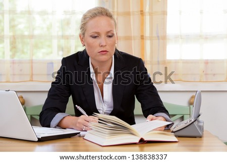 successful young businesswoman sitting at desk with laptop computer and fracture - stock photo