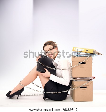 Successful young businesswoman sitting next to pile of documents - stock photo
