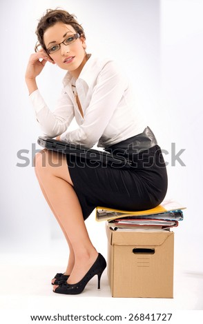 Successful young businesswoman sitting on pile of documents - stock photo