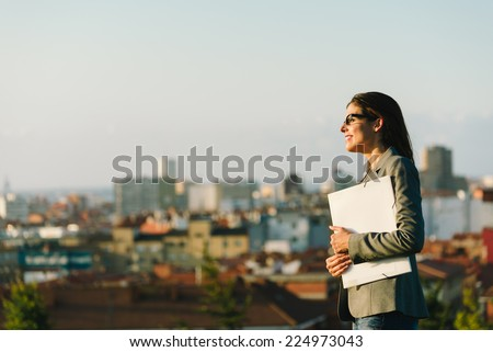 Successful young businesswoman towards city background. Professional happy woman walking outside. - stock photo