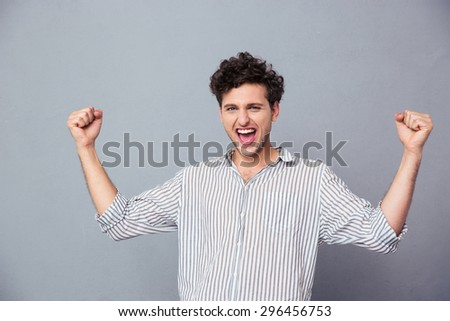 Successful young man celebrating his winning over gray background. Looking at camera - stock photo