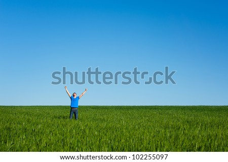 successful young man on the meadow - stock photo