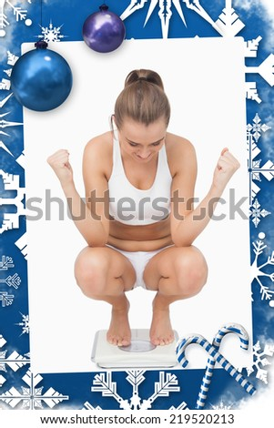 Successful young woman crouching on a scales against christmas frame - stock photo