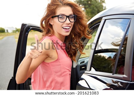 successful young woman in the car with thumb up - stock photo