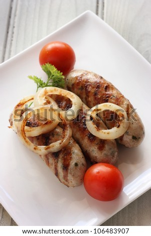 Succulent griddled sausages with onion and tomatoes. Shallow depth of field - stock photo