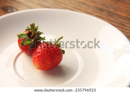 Succulent juicy fresh ripe red strawberries on an old wooden textured table top - stock photo