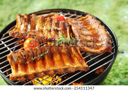 Succulent spicy spare ribs on a barbecue grilling over the hot coals with fresh rosemary and thyme and cherry tomatoes, outdoors on grass - stock photo