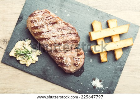 Succulent thick juicy portions of grilled fillet steak served with potatoes and sauce of mushrooms on a slate plate  - stock photo