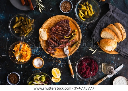 Succulent thick juicy portions of grilled fillet steak served with variety veggies dips, fermented veggies, cucumber and pepper marinated, bread buns on a old vintage table  Authentic dinner party. - stock photo