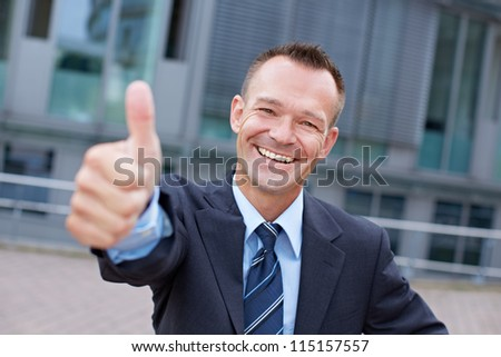 Sucessful smiling business manager holding his thumbs up - stock photo