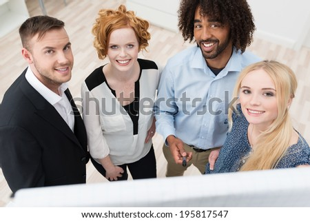 Sucessul young diverse multiethnic business team standing in front of a flip chart discussing their latest project, high angle view - stock photo