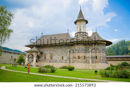 SUCEVITA, ROMANIA - 8 AUGUST 2014: SUCEVITA orthodox Monastery in Moldavia Region of Romania famous for it's painted religious scenes on the wall on a sunny summer day with a green garden - stock photo