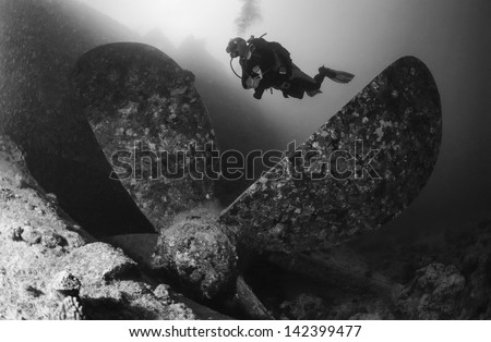 SUDAN, Red Sea, U.W. photo, Umbria wreck, a diver close to one of the propellers of the sunken ship - FILM SCAN - stock photo