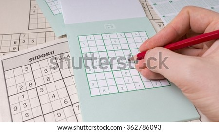 Sudoku puzzle and hand with pencil. - stock photo