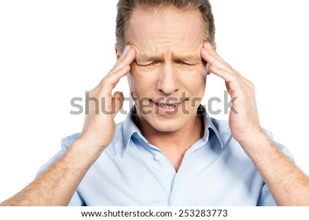 Suffering from headache. Frustrated mature man touching head with fingers and keeping eyes closed while standing against white background - stock photo