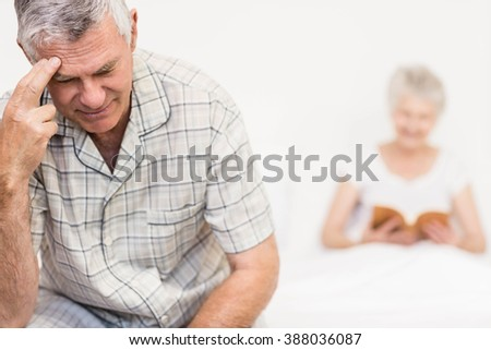 Suffering senior man touching his forehead at home - stock photo