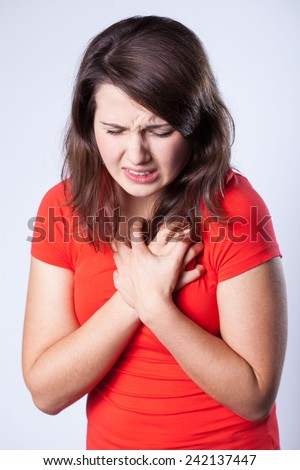 Suffering young woman having pain in chest - stock photo