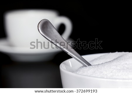 Sugar bowl with teaspoon.  Coffee cup behind.  Dark background. - stock photo