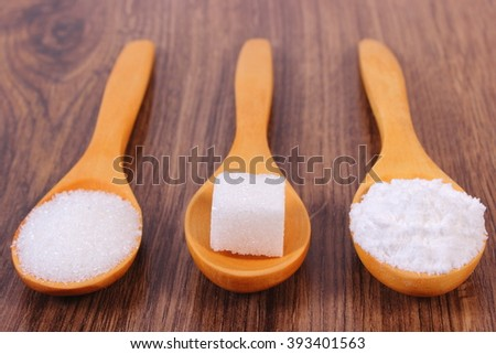 Sugar cube, granulated and powdered sugar on wooden spoons, ingredient for cooking or baking - stock photo