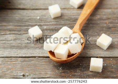 Sugar cube in spoon on grey wooden background - stock photo